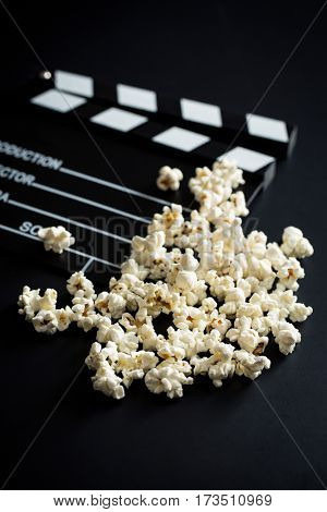Clapperboard and popcorn on black background.