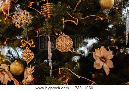 Christmas tree decorated with garlands, stars, flower, sweet and Christmas lights on the background of beautiful bokeh.