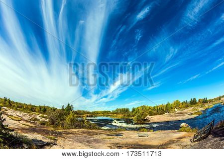 Thin flying cirrus clouds over narrow and rough Winnipeg River, Old Pinawa Dam Park. On the shore is a wooden bench for tourists. The concept of ecological  tourism
