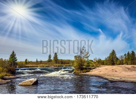 Waterfall drain on the smooth stones of the Winnipeg River. Weak northern autumn sun. The concept of ecological and extreme tourism tourists