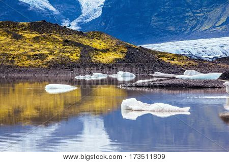 Summer in Iceland.  The cold lake with splinters of ice floes formed by thawed snow of glacier Vatnajokull.  The concept of northern tourism.