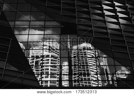 Sydney, Australia - 7 February, 2016; Distorted reflections of Sydney CBD buldings and Centrepoint Tower within the windows of a new building under construction in Sydney.  . Black and White.