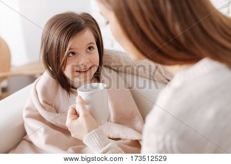 Little improvements. Pleasant cheerful little girl smiling and looking at her mother while recovering from flu