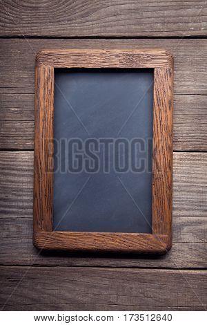 old school blackboard on a background of blackened wood panels