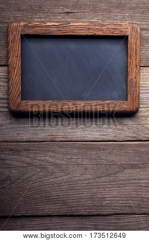 old school blackboard on a background of blackened wood panels