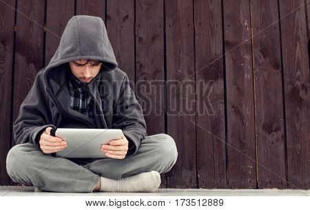 teenager with a tablet computer at the wooden walls, a hacker sitting on the floor looks on the screen Message