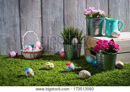 Easter eggs painted on a wooden background of boards on green grass.
