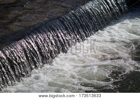 Sluice with stream on the creek in nature