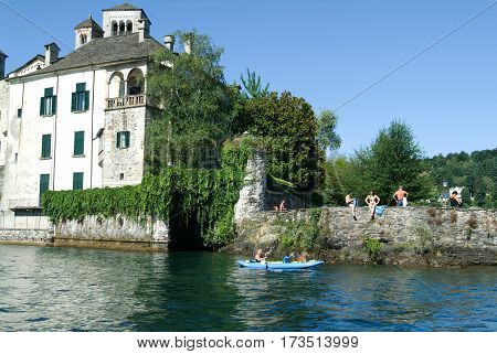 People Rowing On A Canoe In Front Of San Giulio Island