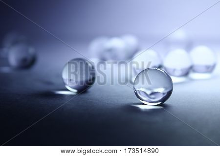 Round, transparent balls on a blue background. Soil for flowers.