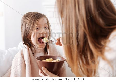 Healthy and tasty. Joyful cute little girl eating breakfast with mother and expressing gladness while resting together