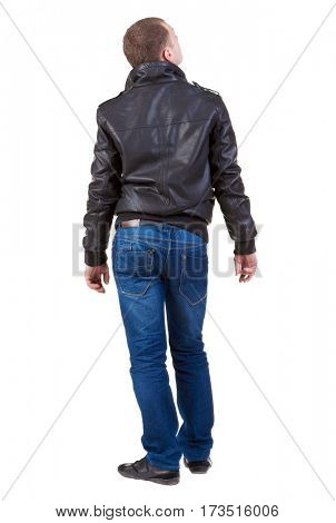 Back view of handsome man in jacket looking thoughtfully into the distance.   Standing young guy in jeans and  jacket. Rear view people collection.