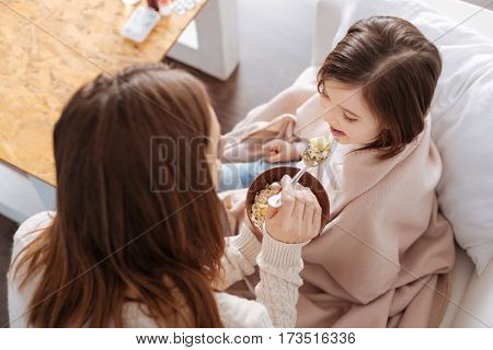 Positive atmosphere. Pleasant loving mother feeding her daughter with outmeal while resting together at home