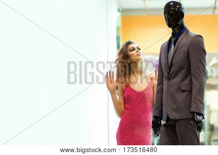 Pretty Girl Looks At Male Mannequin In Shop Window