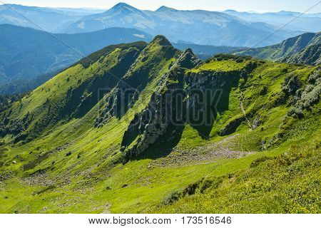 Rocky Ridge Among The Green Alpine Meadows