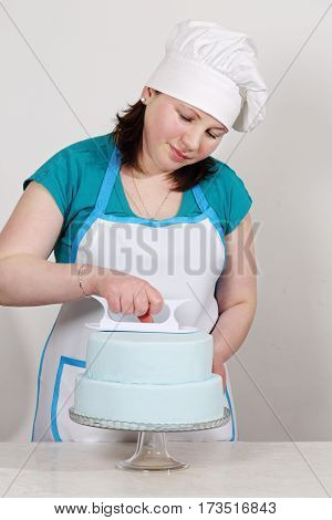 Chef smoothes mastic on the cake on a white background