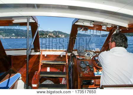 Captain Driving A Boat In Front Of San Giulio Island
