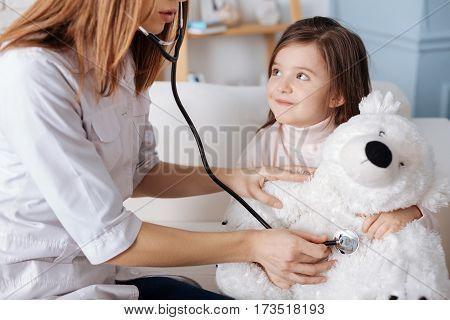 My little friend. Professional female doctor using stethoscope and examining fluffy bear while sitting on the couch