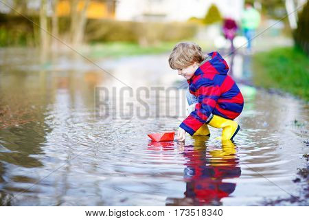 Happy little kid boy in yellow rain boots playing with paper ship by a puddle on spring or autumn day. Active leisure for children. Child having fun outdoors and wearing colorful clothes.