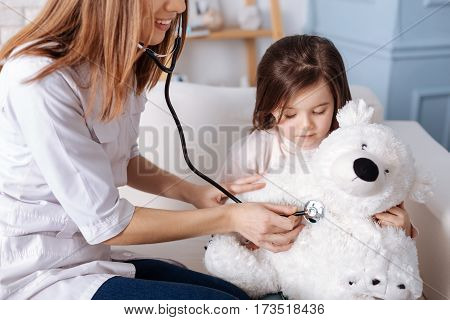 One more visit. Cheerful pleasant professional doctor examining fluffy toy of little girl while sitting on the couch and expressing joy