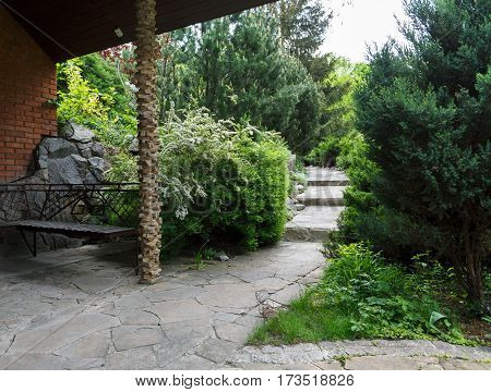 Beautiful landscape design, garden path with staircase in stone tiles, evergreen bushes and shrubs in sunlight. Bench in beautiful park. Summer yard design.