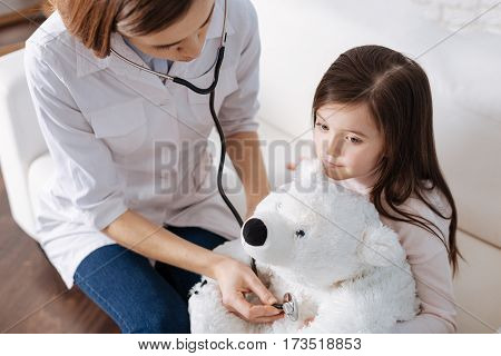 Pleasant atmosphere. Pleasant loving mother pretending to be a doctor and examinign fluffy toy of her daughter