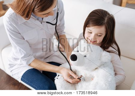 Deep breath. Pleasant loving mother examining with stethoscope fluffy toy of her daughter while pretending to be a doctor