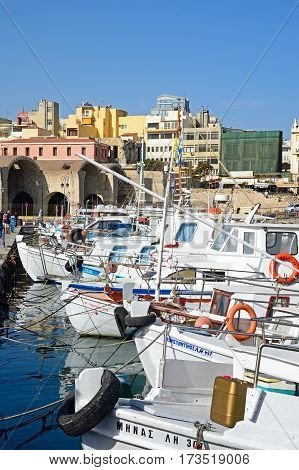 HERAKLION, CRETE - SEPTEMBER 19, 2016 - Fishing boats and yachts moored in the harbour with waterfront buildings to the rear Heraklion Crete Greece Europe, September 19, 2016.