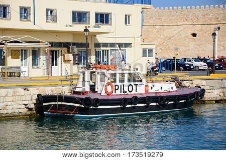 HERAKLION, CRETE - SEPTEMBER 19, 2016 - Pilot boat in the port with the Hellenic Coastguard building to the rear Heraklion Crete Greece Europe, September 19, 2016.