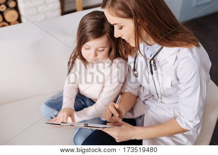 Just look. Joyful pleasant female doctor making notes and making prescriptions for little sick girl