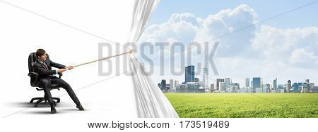 Businessman sitting in chair and pulling white blank fabric. Place for text