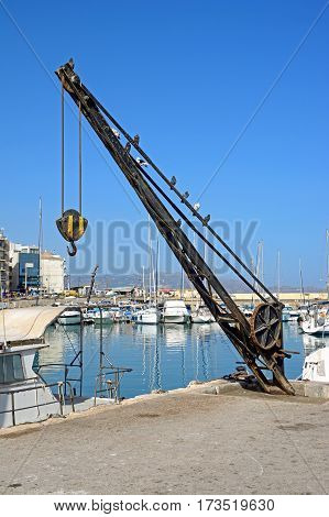 HERAKLION, CRETE - SEPTEMBER 19, 2016 - Dockside crane on the quayside with yachts and boats moored to the rear Heraklion Crete Greece Europe, September 19, 2016.
