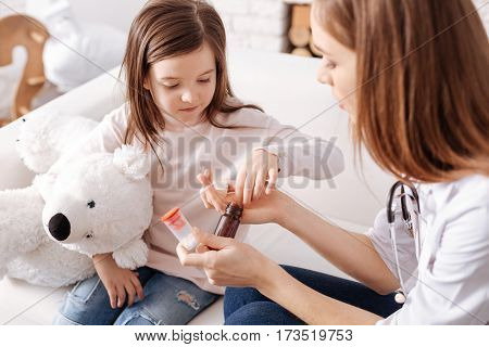 Your dose. Sick little girl takign pills while professional doctor assisting her while sitting on the couch together