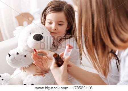Take it every day. Professional female doctor holding pills and giving to a little girl while she is holding her fluffy toy