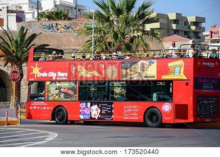 HERAKLION, CRETE - SEPTEMBER 19, 2016 - Passengers on a red open topped tour bus parked near the port Heraklion Crete Greece Europe, September 19, 2016.