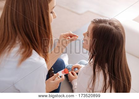 And one more. Pleasant professional pediatrician giving pills to her little patience while sititng on the couch together