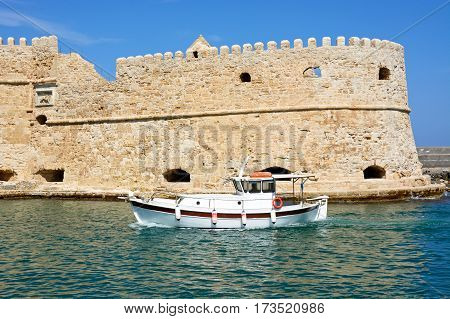 HERAKLION, CRETE - SEPTEMBER 19, 2016 - View of Koules castle with a boat in the foreground Heraklion Crete Greece Europe, September 19, 2016.
