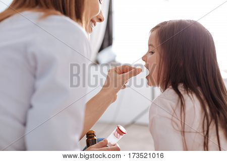 Daily take. Cheerful professional doctor smiling and giving pills to her patient while helping to recover