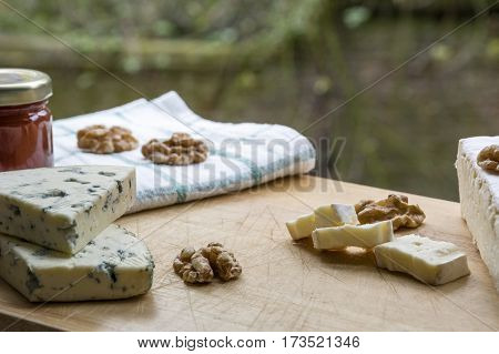 Several tasty pieces of brie and roquefort cheese with nuts and jam
