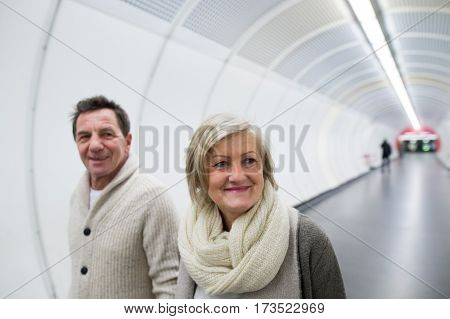 Beautiful senior couple in winter clothes walking in the hallway of subway in Vienna