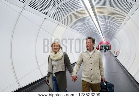 Beautiful senior couple walking in the hallway of subway in Vienna pulling a trolley luggage.