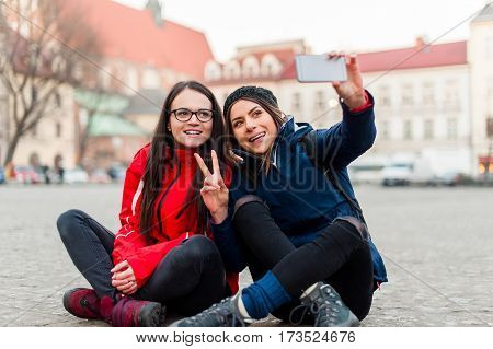Two girlfriends taking a self portrait, sitting on the street in a touristic city center, while visiting the city and having fun showing victory sign.