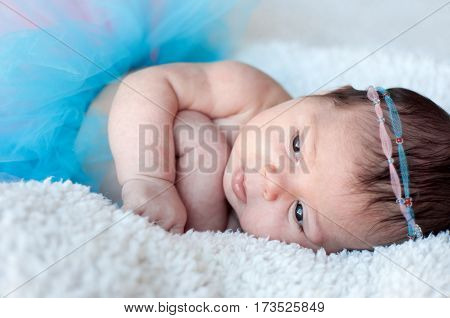 Newborn baby girl. Portrait of a newborn girl with a fluffy skirt and the pink - blue Headbands with beads.