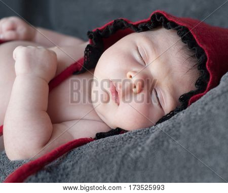 Newborn Baby Closeup In A Red Cap. Close-up Portrait Of A Beautiful Sleeping Baby.  Photo With Selec