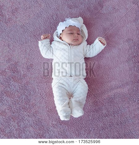 Newborn baby on a purple background picture from the top. Newborn. Kid warmly dressed.