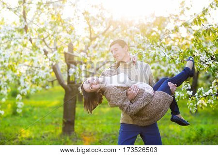 Portrait of a happy pregnant couple in the blossom garden