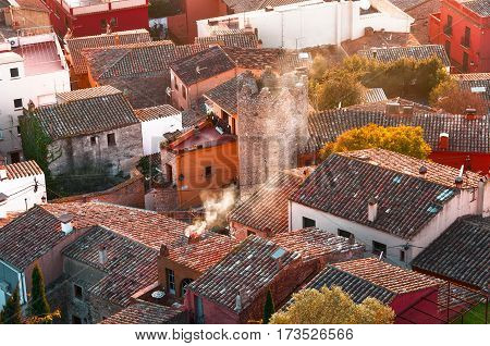 Top view of a small town in Spain Begur. Detail view of traditional European town roofs and houses. Smoking chimneys in city.