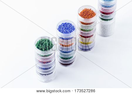 Mix of glass seed beads in glass tubes for jewelry making and beading process on white background. Hobby handmade fine arts. Selective focus.