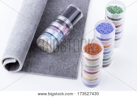 A raw of colord seed beads in glass tubes and grey beading mat for beading on white background. Selective focus.