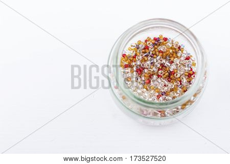 Mix of glass seed beads for jewelry making and beading process on white background. Hobby handmade fine arts. Selective focus.